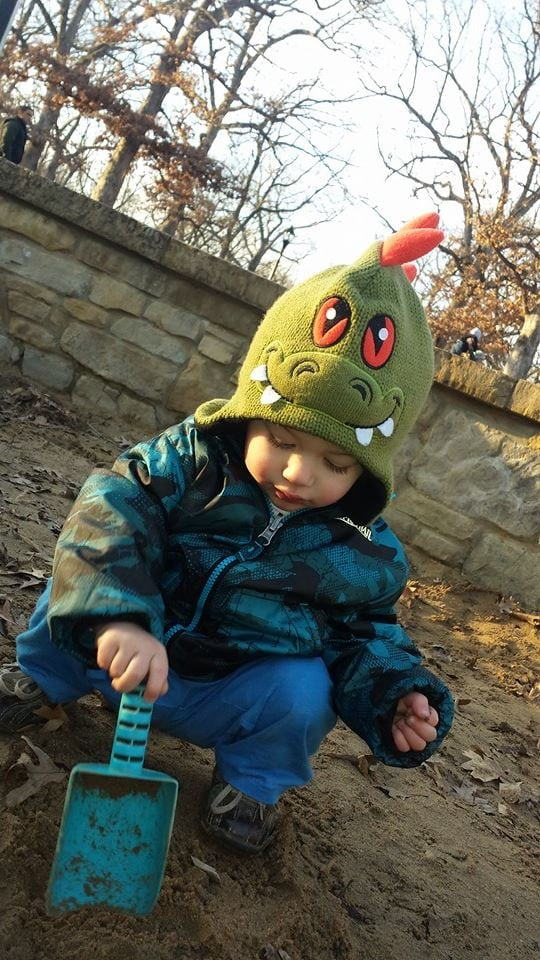 toddler digging in sand wearing a green and orange monster hat