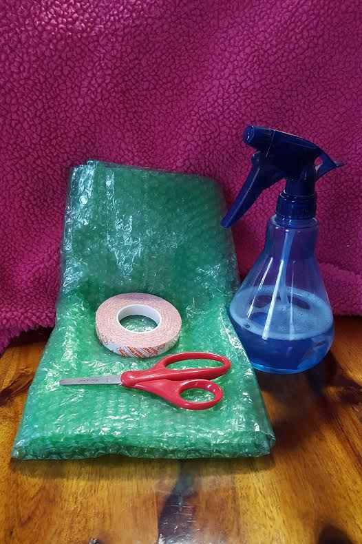 blue water bottle next to green bubblewrap and red scissors
