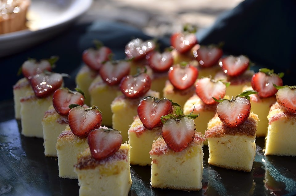 squares of cheesecake with halved strawberries on top