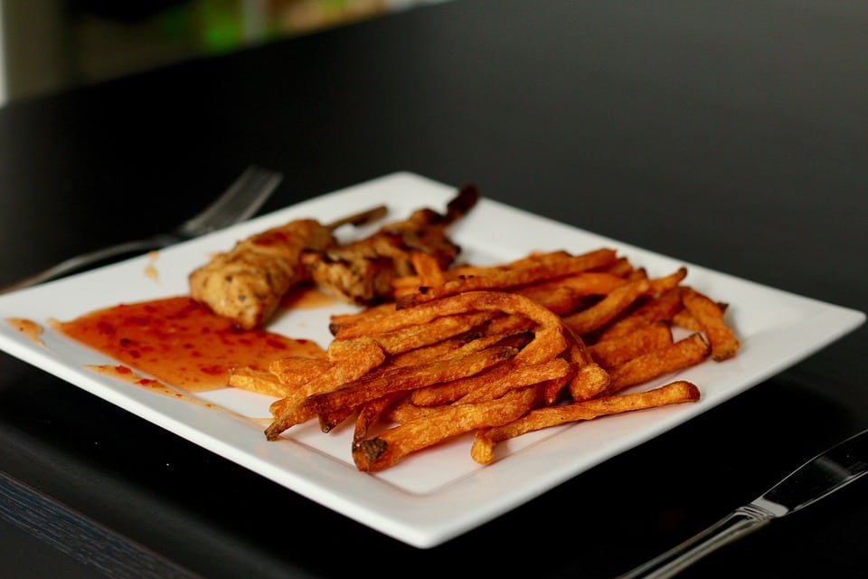 chicken tenders and sweet potato fries on a white square plate