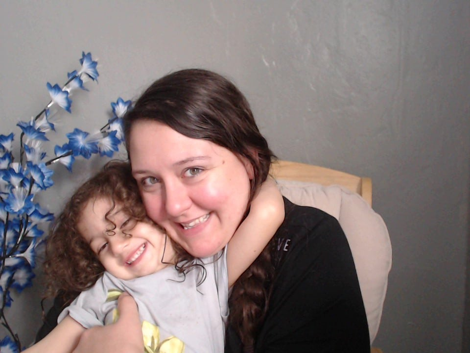 curly hair brown hair toddler hugging her brunette mom