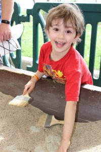 blonde boy playing in sand at jurassic quest