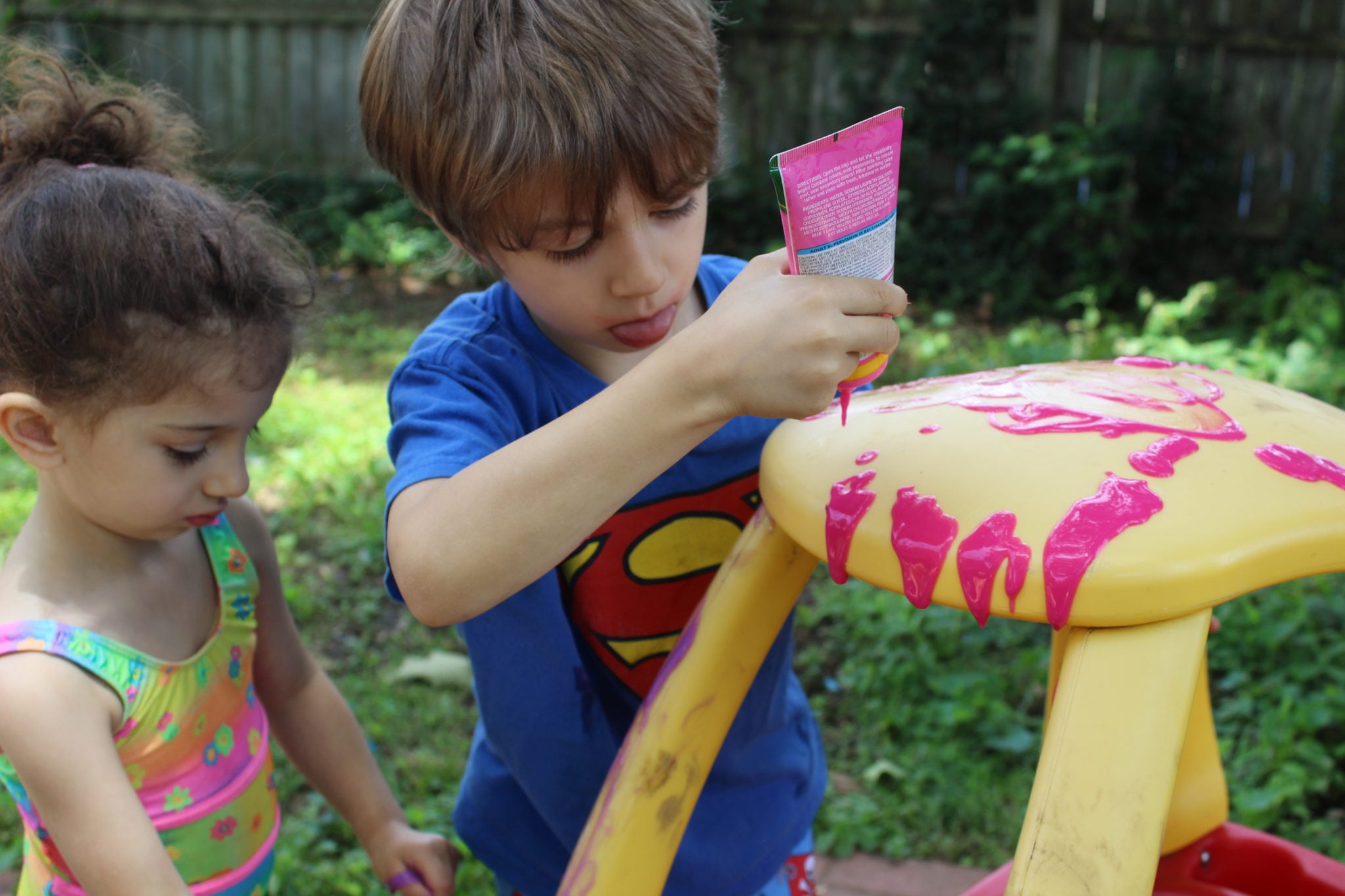 blonde toddler in blue superman shirt sticking his tongue out as he puts pink bath paint on toy car
