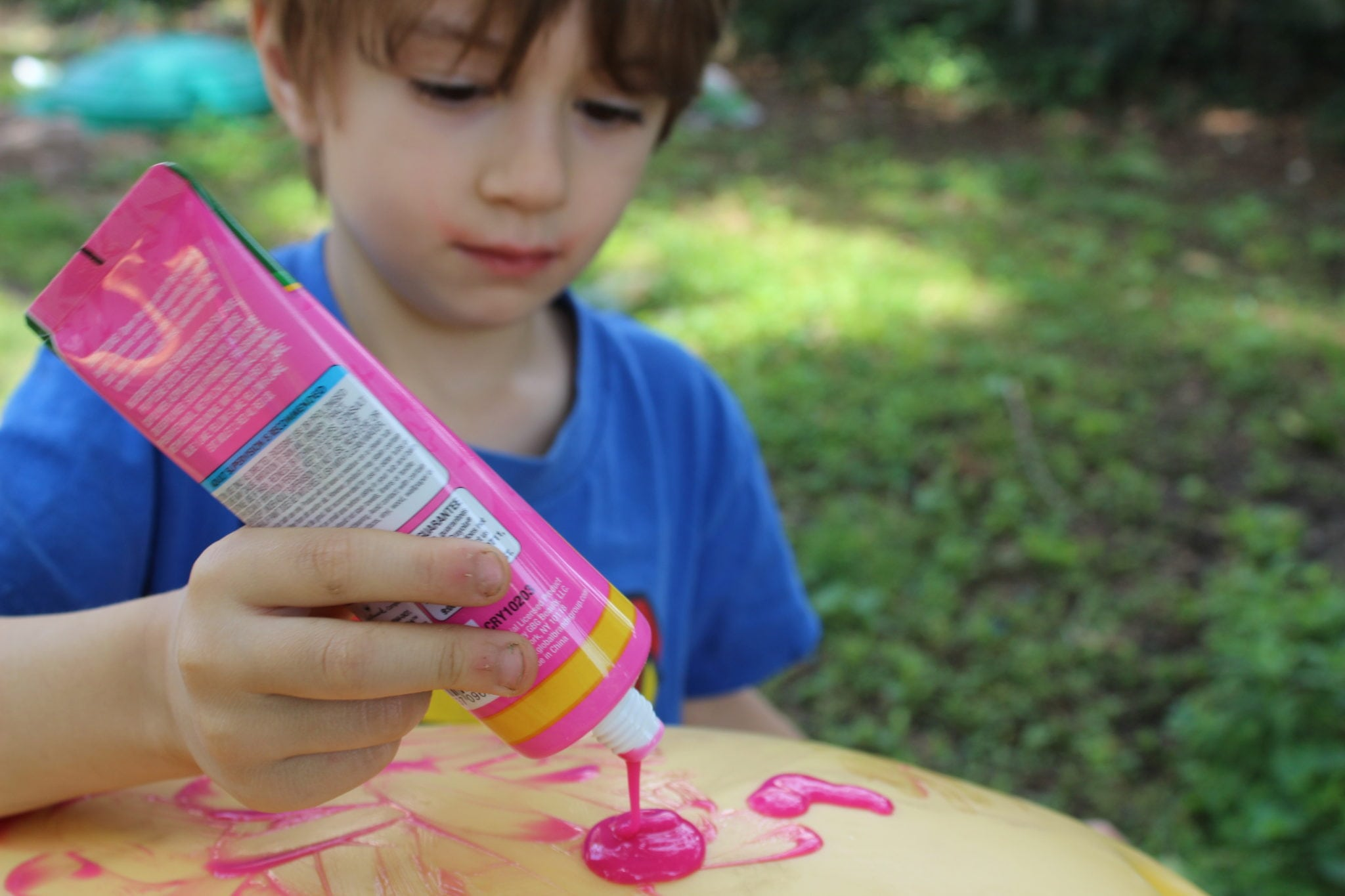blonde toddler squeezing pink bath paint on yellow toy car