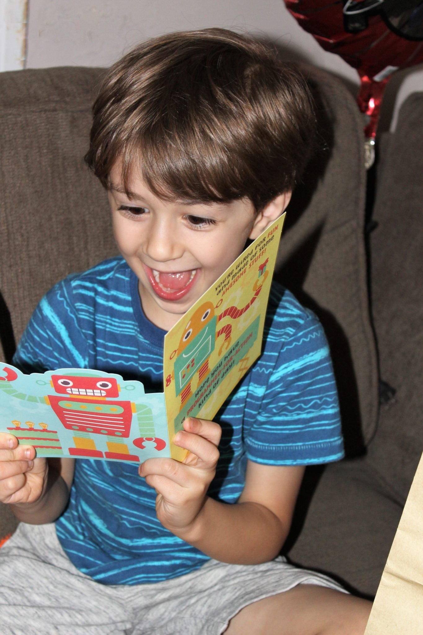 blonde hair preschool boy in blue shirt looking excitedly at a robot birthday card