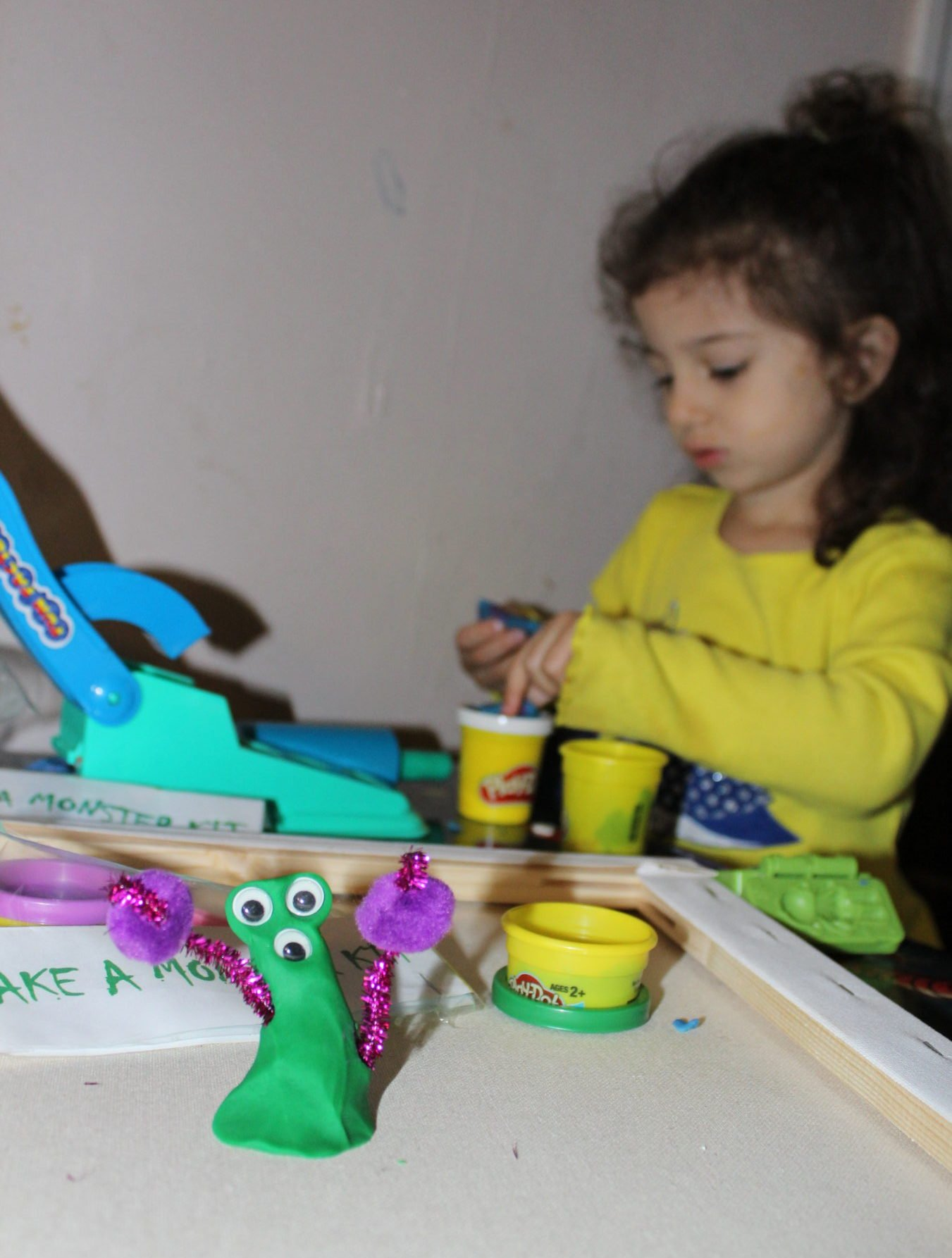 brunette toddler in yellow shirt putting together a play dough monster kit