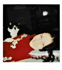 brunette girl in red shirt laying on her back with a black and white cat resting on her stomach