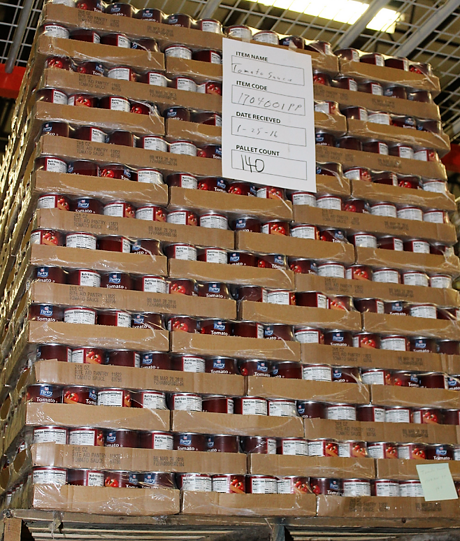 pallet of stacked cans of tomato sauce in cardboard boxes