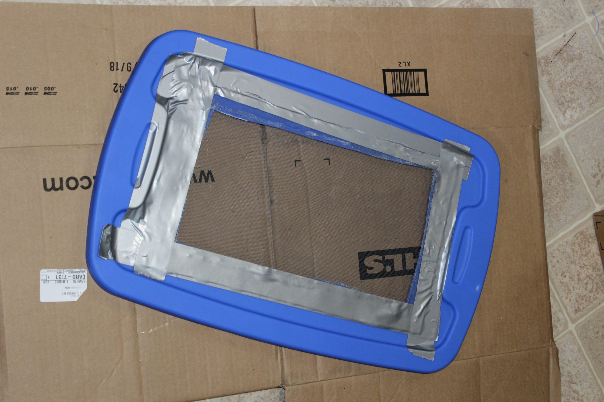 blue tote lid with center cut out and replaced by a screen and duct tape around edges holding screen in place