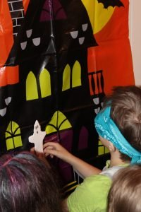 Blonde boy child wearing blue bandana over his eyes trying to play pin the tail on the ghost