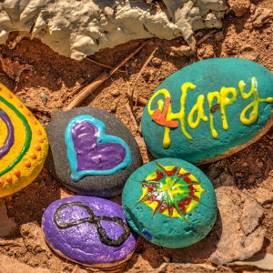 a green painted rock with the word happy written in yellow paint