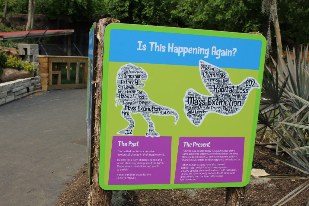"Blue and green sign that says ""Is this happening again"" and compares the past to the present in terms of extinction"