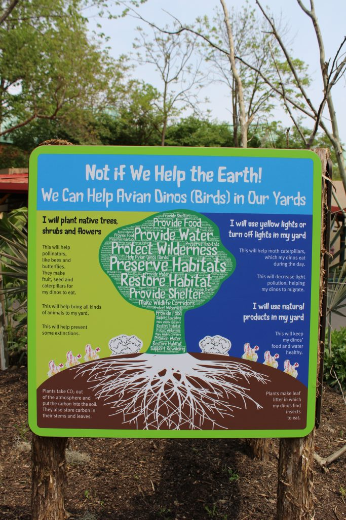 "Blue sign that says ""Not if we help the earth! We can help avian dinos (birds) in our yards"""