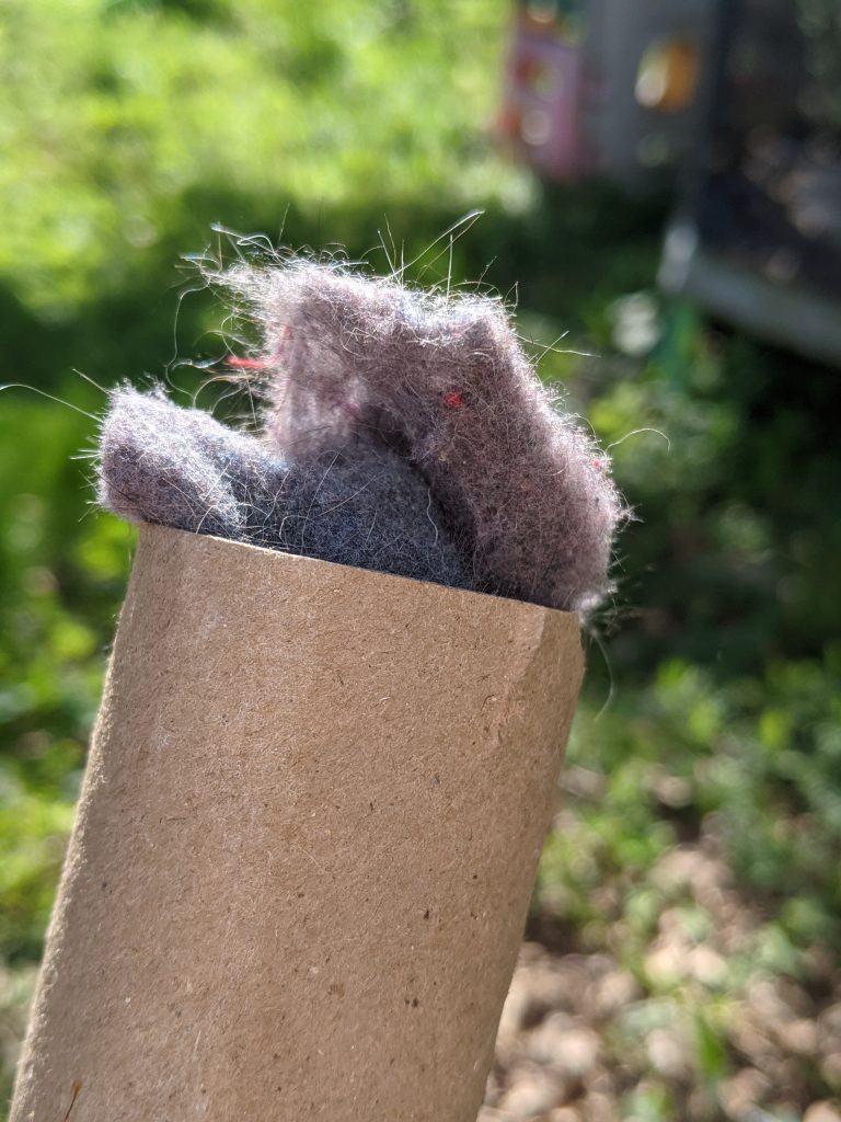 Toilet paper tube with tufts of dryer lint sticking out